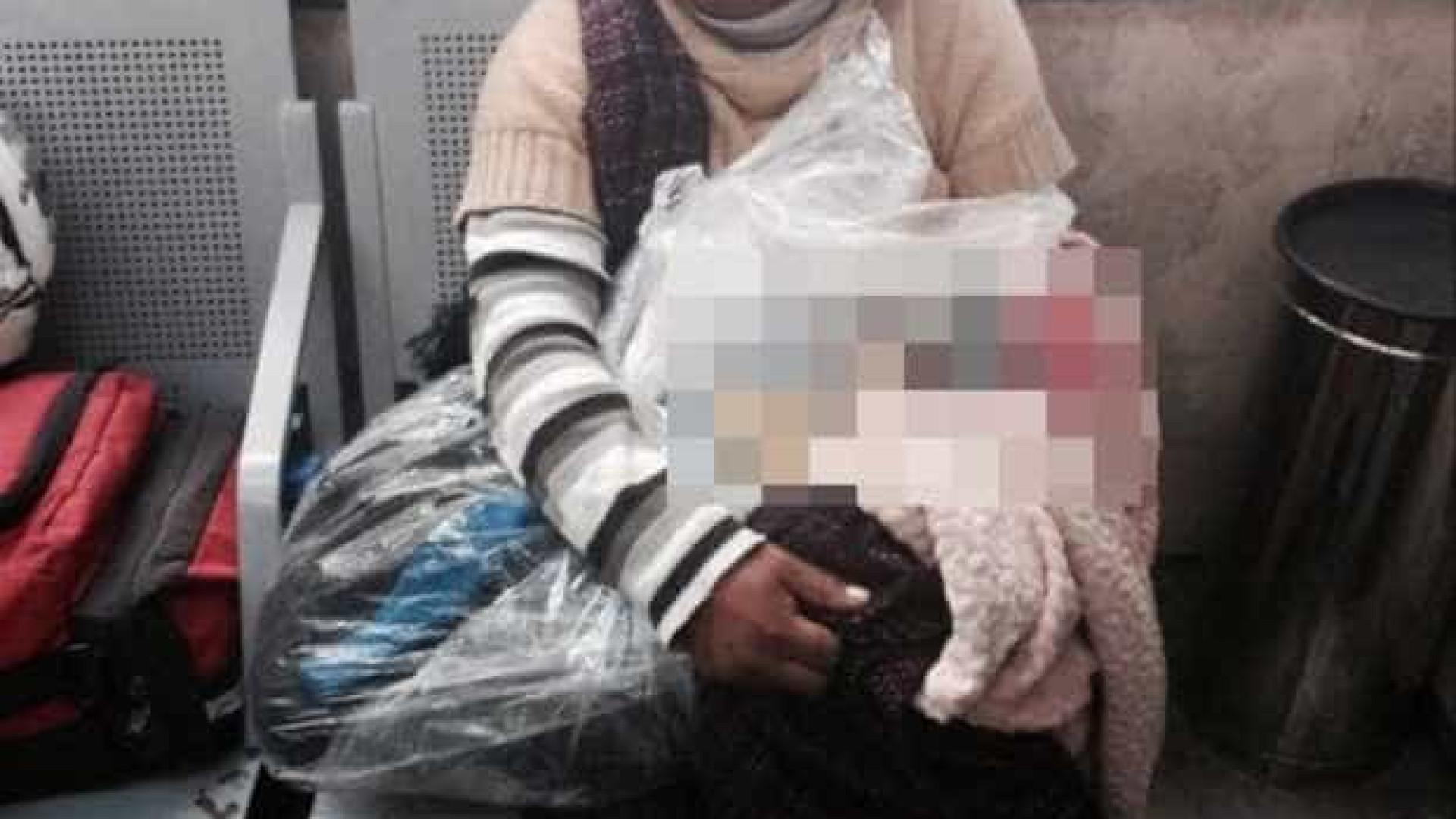 Mãe transporta corpo do filho enrolado em plástico para casa