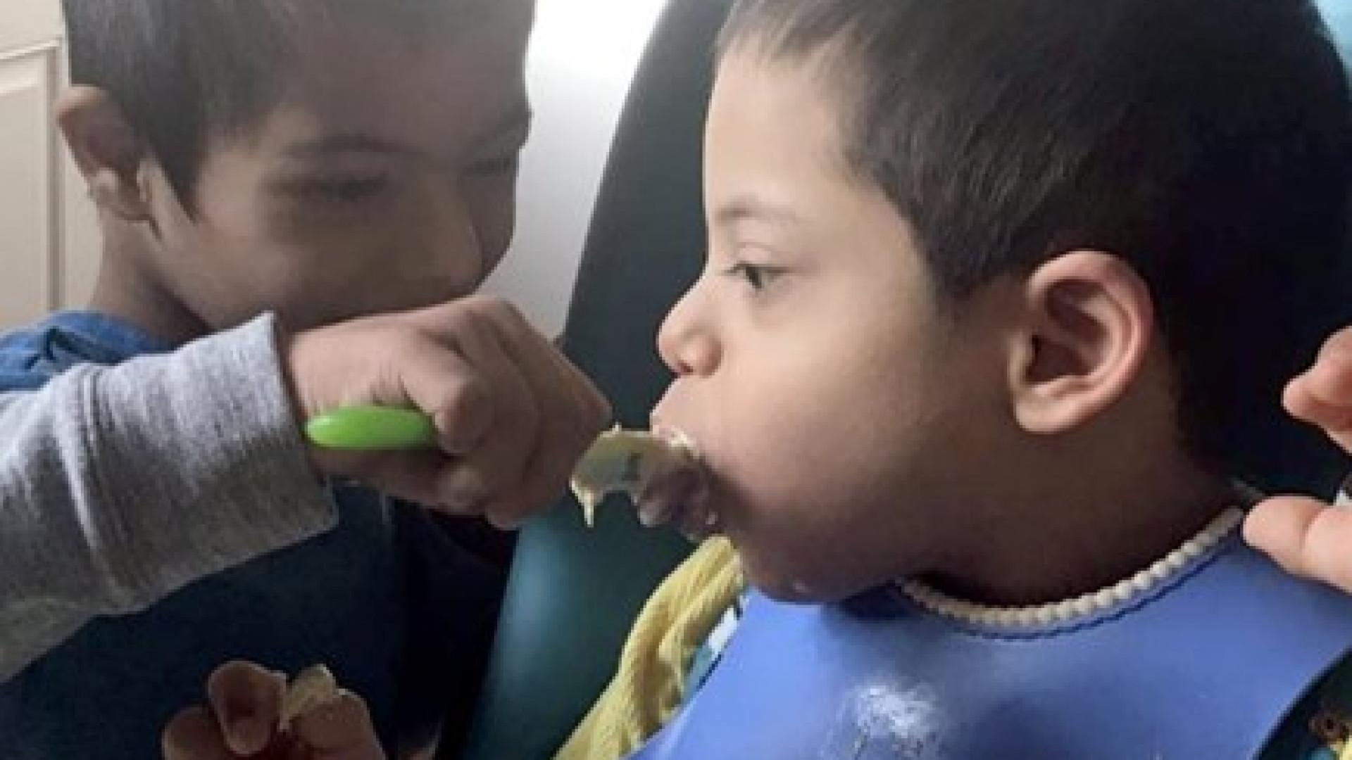 Menino com Síndrome de Down ajuda os irmãos a comer e a vestir