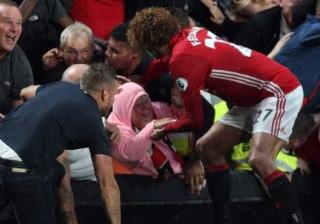 Enquanto colegas festejavam, Fellaini impediu adepta de ser esmagada