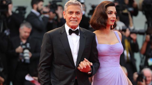 Jornal diz que George e Amal Clooney serão os padrinhos do bebé de Harry