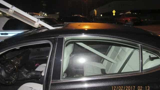 Mulher embriagada conduz com sinal de trânsito preso carro