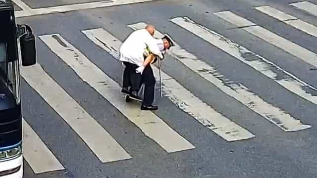 Vídeo emocionante mostra polícia a carregar idoso às costas em passadeira
