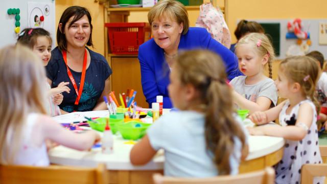 Cómico: Merkel sorri com crianças sem imaginar o que está atrás de si