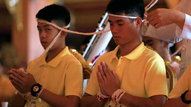 Crianças e treinador em cerimónia budista para os proteger de infortúnios