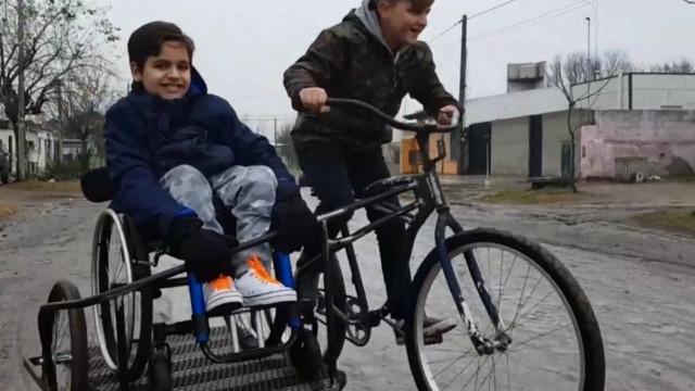 Menino criou bicicleta com sidecar para levar primo em cadeira de rodas