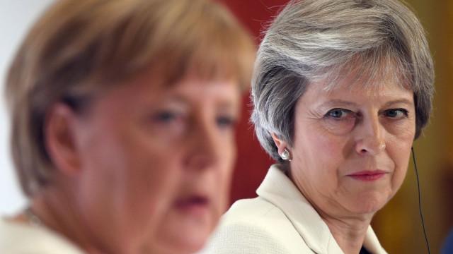 Brexit: May vai pedir ajuda a Merkel para mudar acordo de 'divórcio'