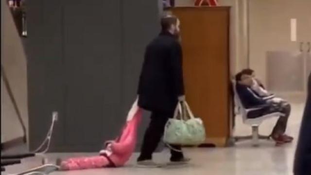 Farto de birras, pai arrasta filha pelo capuz do casaco em aeroporto