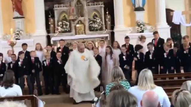 Padre junta-se a crianças em altar da Igreja para dançar