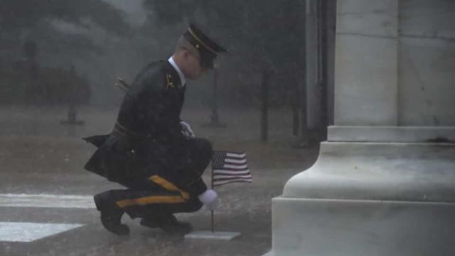 Nem a chuva torrencial o impediu de colocar bandeira em túmulo de soldado