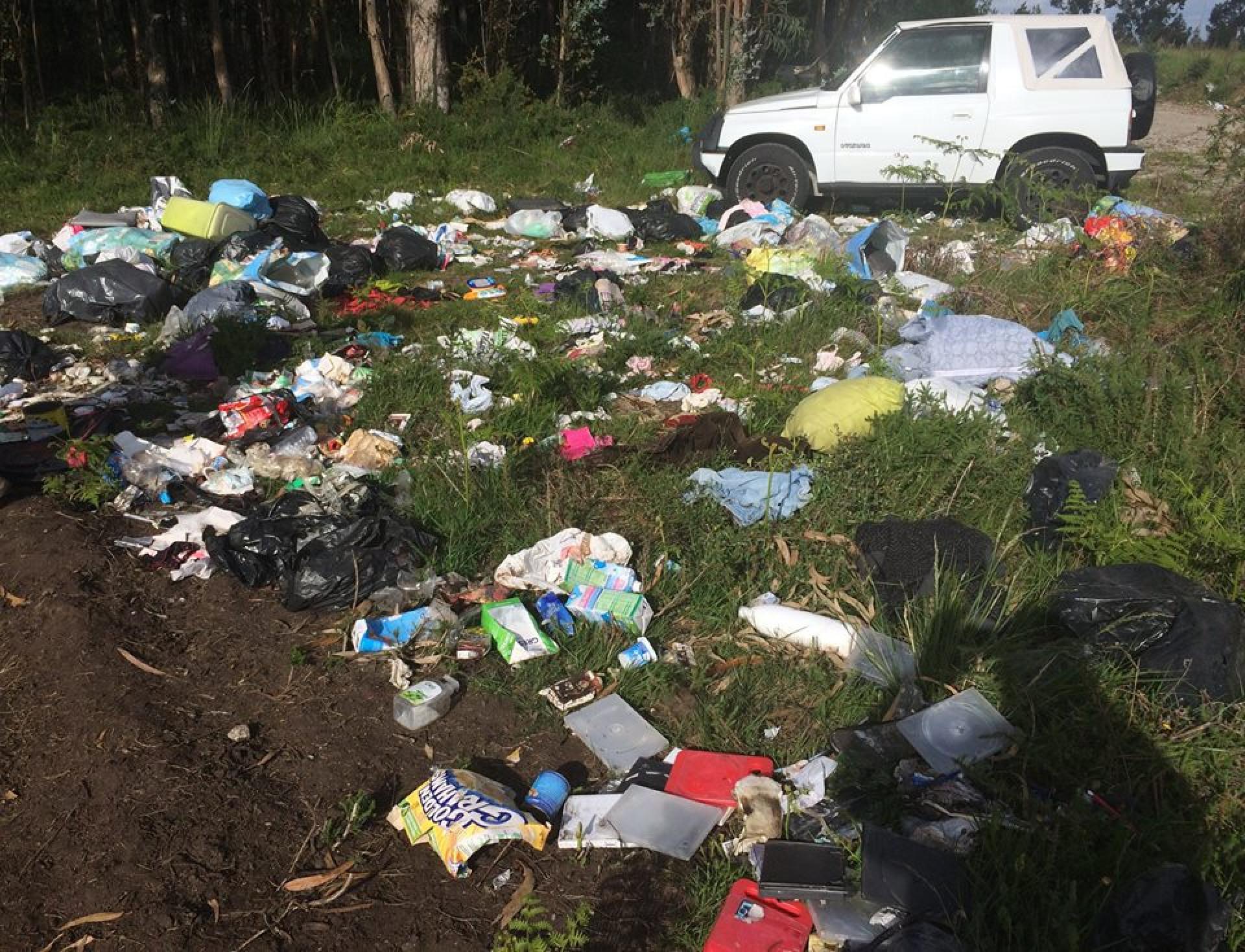Grandes quantidades de comida, roupa e lixo abandonadas em terreno baldio