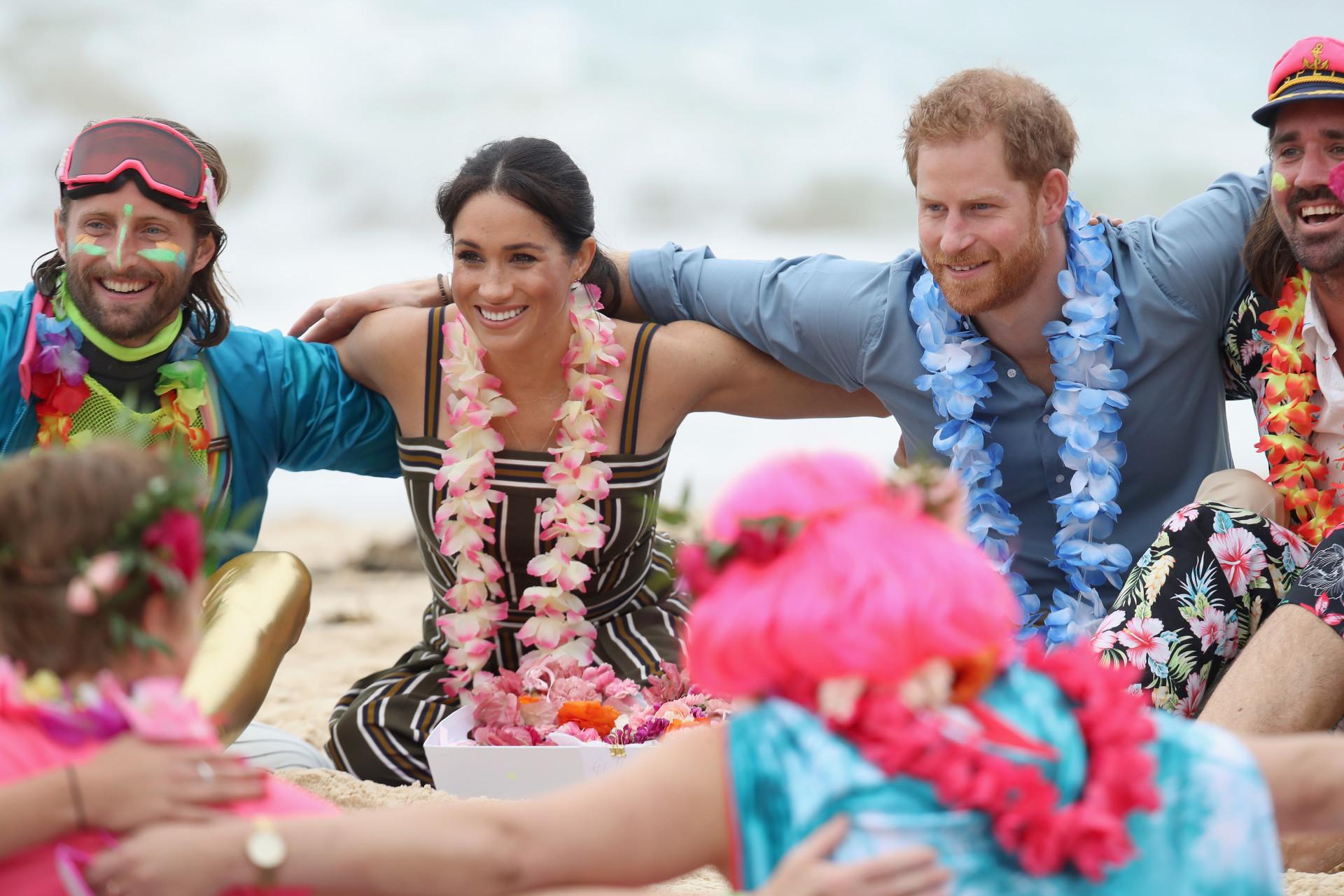 Pé na areia e coroas de flores: A visita oficial de Meghan Markle e Harry