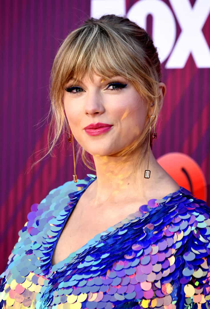 Taylor Swift 'brilha' na passadeira vermelha com cabelo cor de rosa